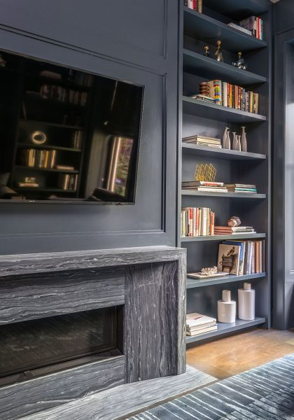 blue bookshelves, blue den, built in bookshelves around fireplace